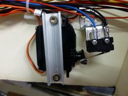 Bild eines montierten Rückmelders am Servo. Das Schaltsignal (gegen Masse) wird via Blücher Rückmelder an das System gemeldet. Im Traincontroller (Steuerungssoftware) wird für jede Weiche die Rückmeldung ausgewertet. Traincontroller zeigt die Weiche auch bei manueller Betätigung der Weiche korrekt an. So kriege ich zukünftig keine Probleme, wenn ich die Stellpulte für den manuellen Betrieb einsetze. Führt Traincontroller eine Zugfahrt durch und hat eine Weichenstrasse reserviert worin eine Weiche nicht der geforderten Stellung entspricht, versucht das Programm einen alternativen Weg oder bricht die Zugfahrt ab und meldet die fehlerhafte Weiche. Dies habe ich getestet und war sehr zufrieden mit dem Resultat. Der Aufwand, weniger aus finanzieller Sicht, lohnt sich jedoch für mich.